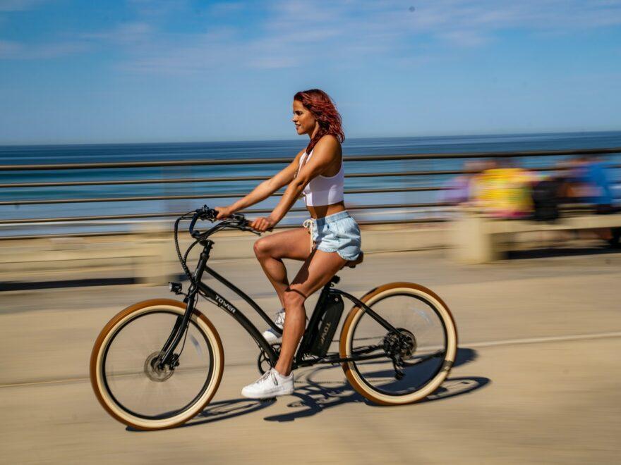 woman in white bikini riding on black bicycle on road during daytime