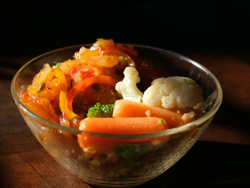 cooked rice with sliced carrots and green vegetable in clear glass bowl