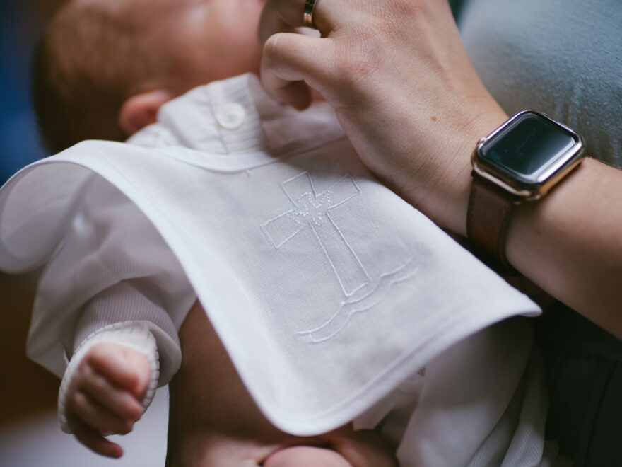 person holding babys white onesie